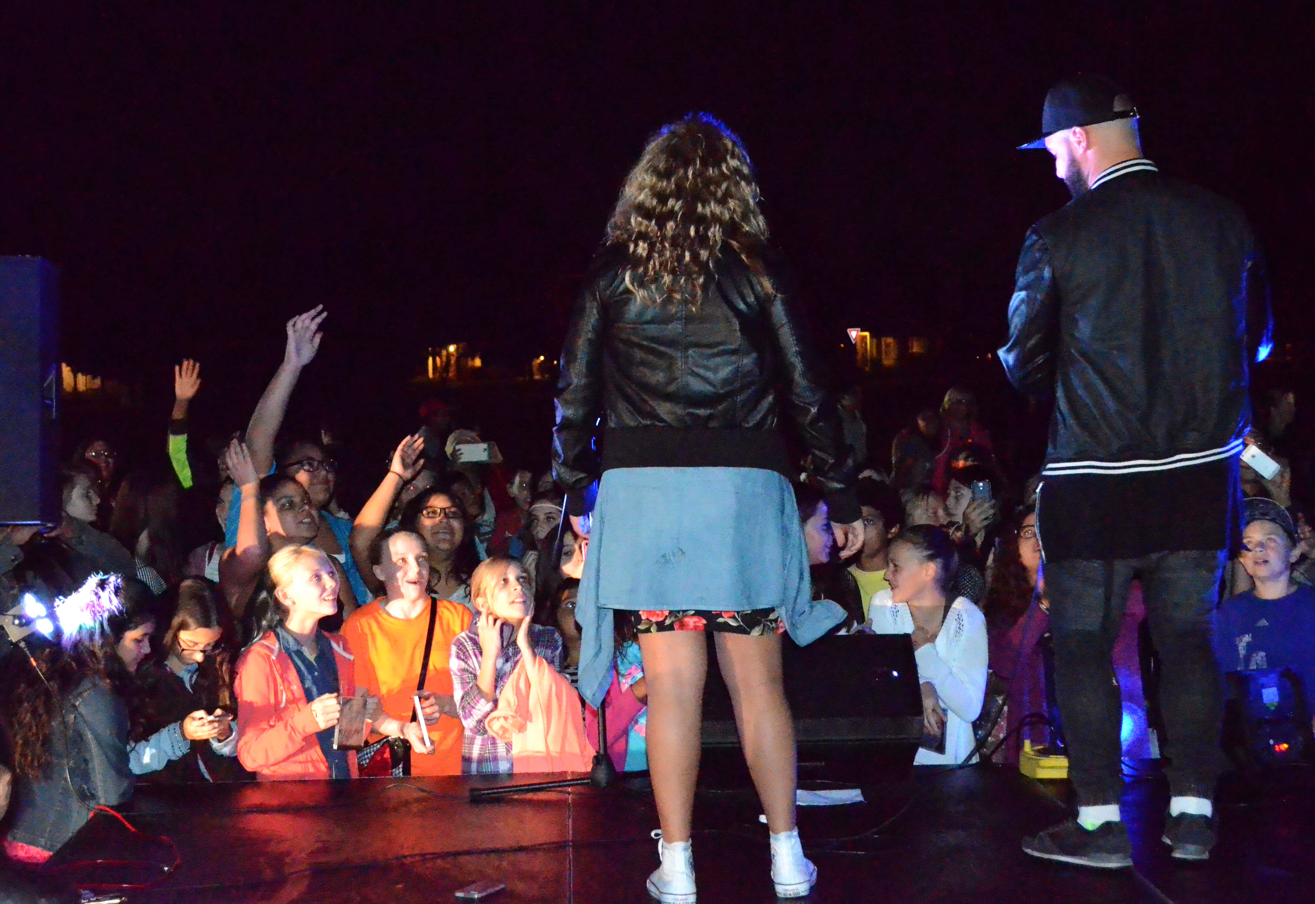 Aaliyah Rose (left) and Mimi Knowles (right) on stage in front of a crowd of Dixon students.