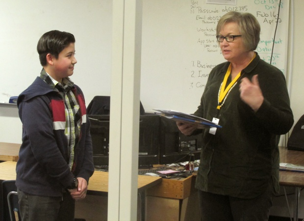 Daryan listening as Karen McMullin explains how his essay won 1st place.